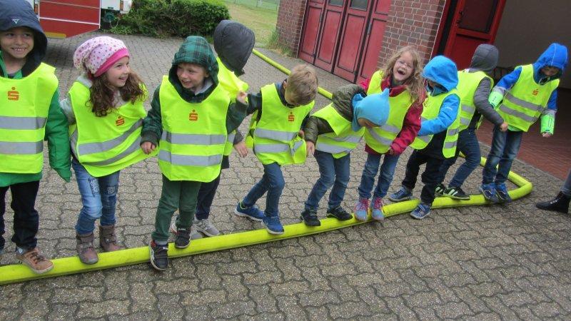 Kinder auf Feuerwehrschlauch